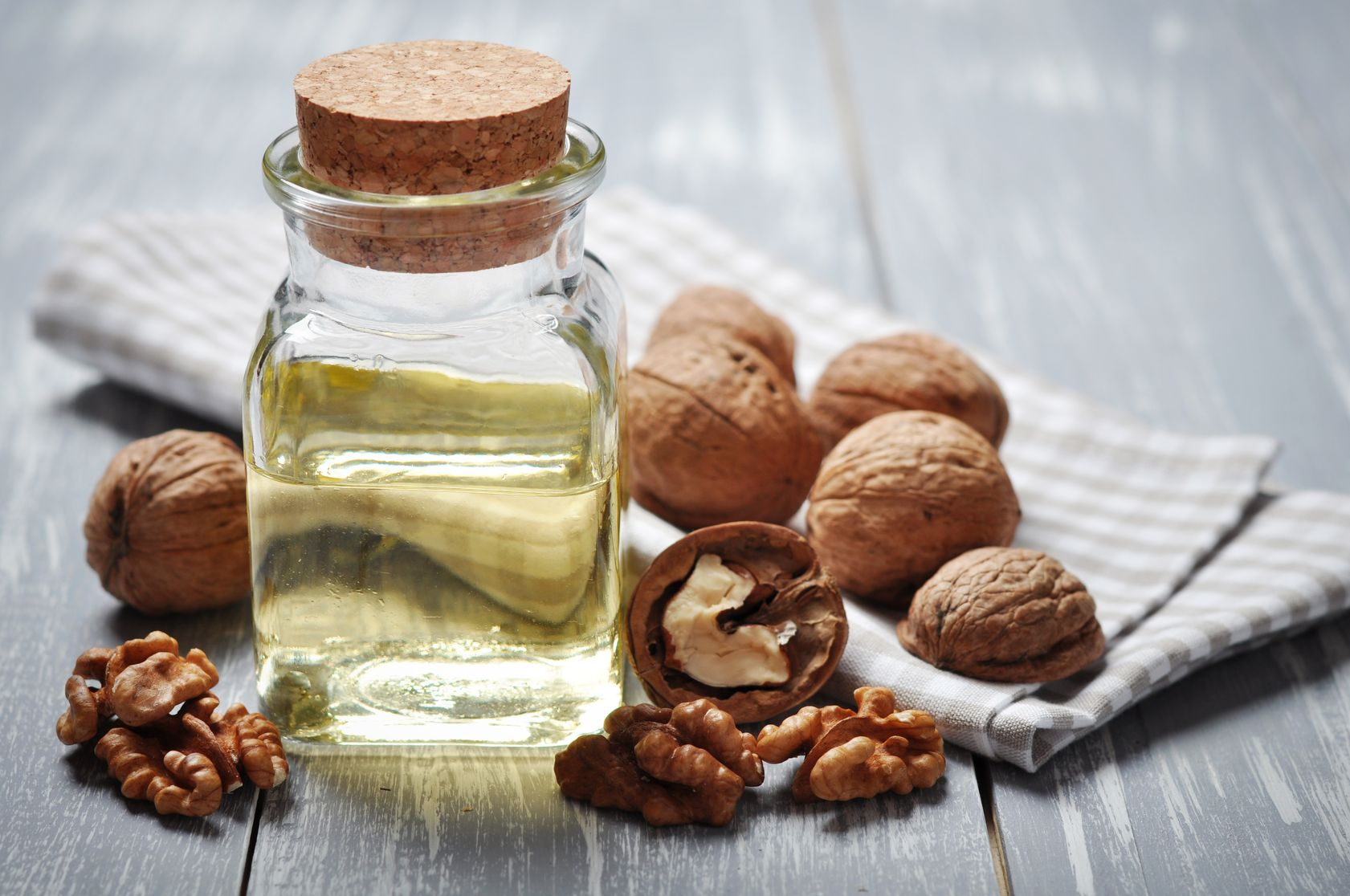 20694995 - walnut oil with nuts on a wooden background