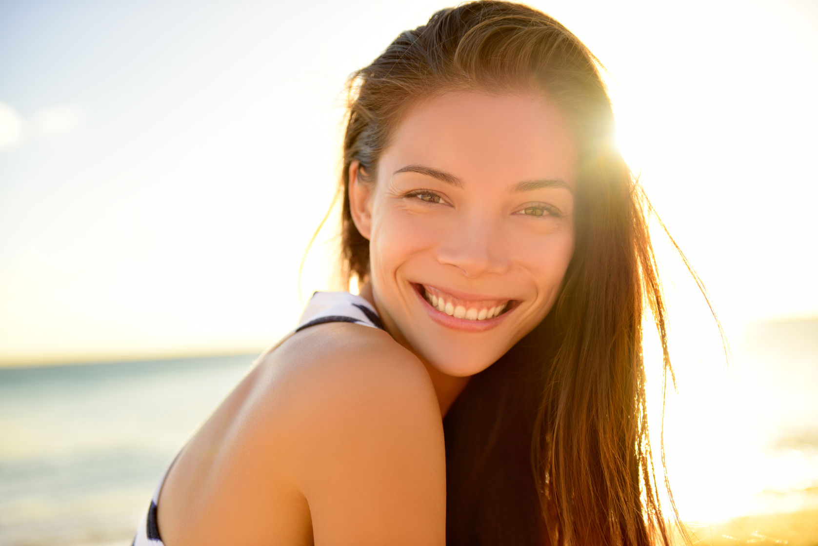36753474 - asian beautiful girl smiling happy on beach vacation enjoying warm sunshine. mixed race asian caucasian pretty model outside with sun in background on hawaiian tropical beach.
