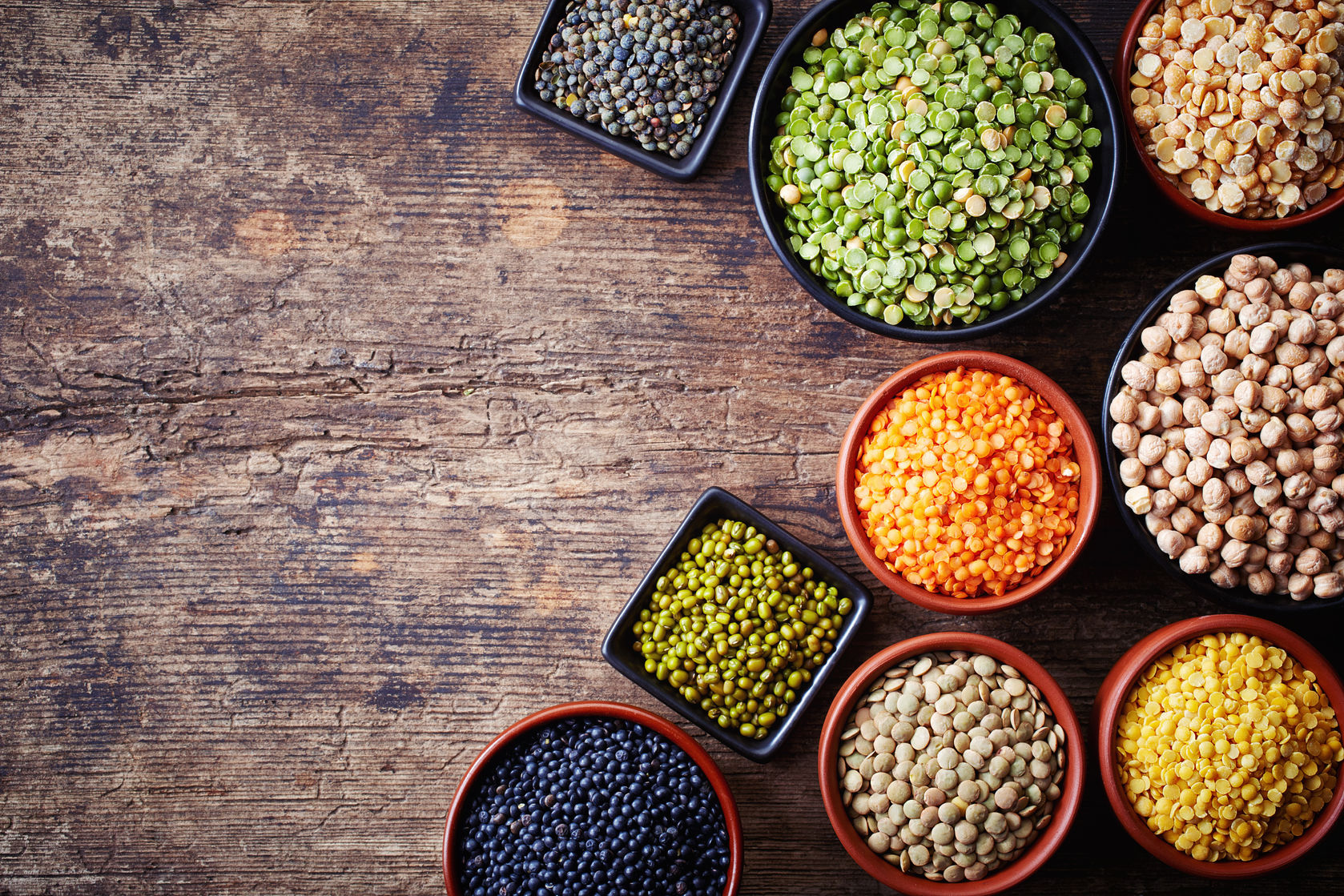 39441429 - bowls of various legumes (chickpeas, green peas, red lentils, canadian lentils, indian lentils, black lentils, green lentils; yellow peas, green mung beans) on wooden background