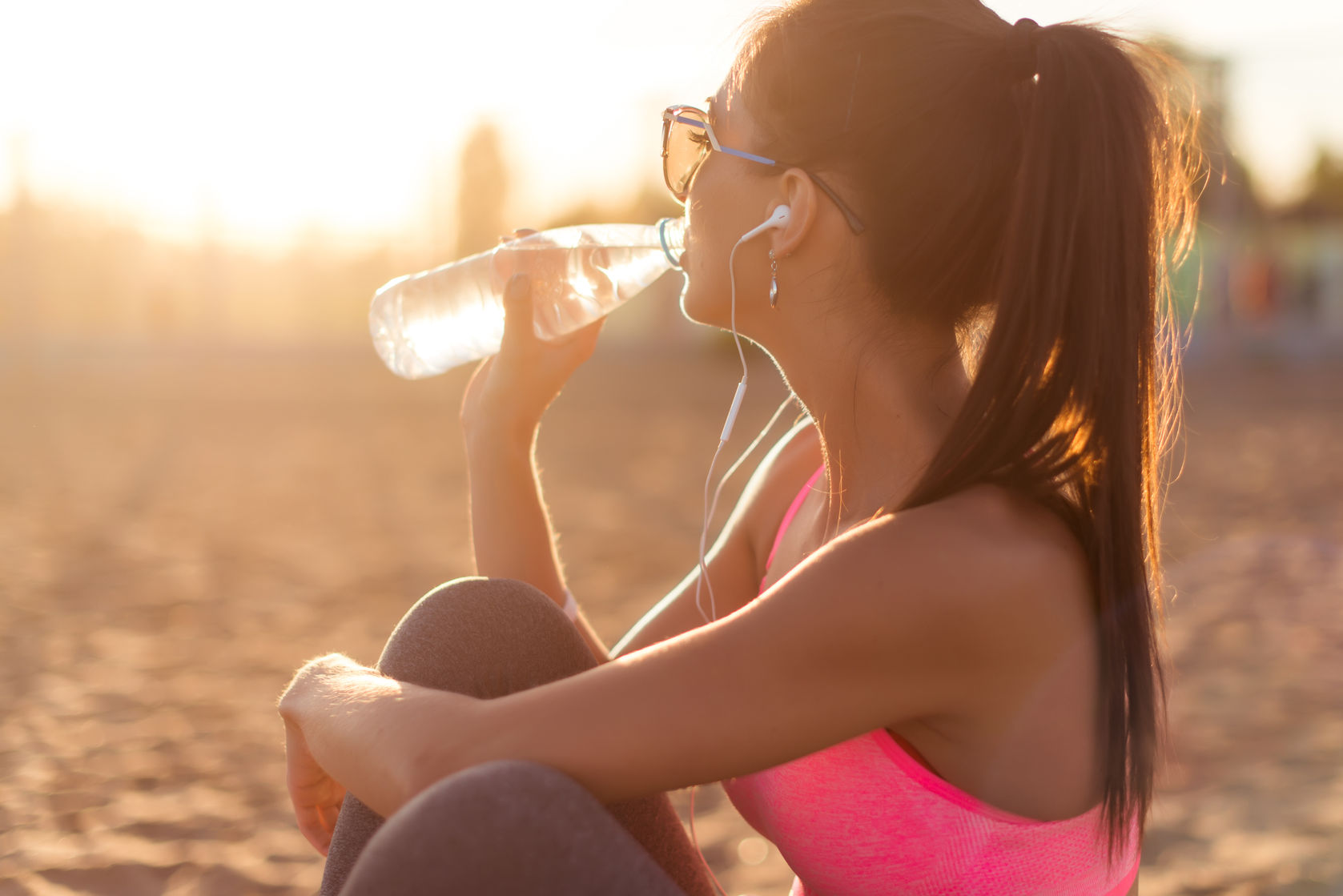 41162100 - beautiful fitness athlete woman drinking water after work out exercising on sunset evening summer in beach outdoor portrait