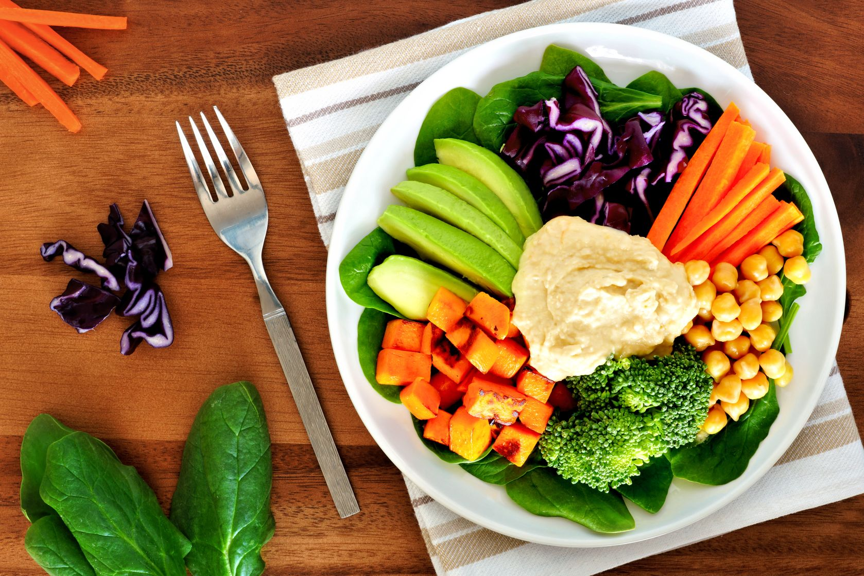 52586093 - healthy lunch bowl with avocado, hummus and fresh vegetables, overhead scene on wooden table