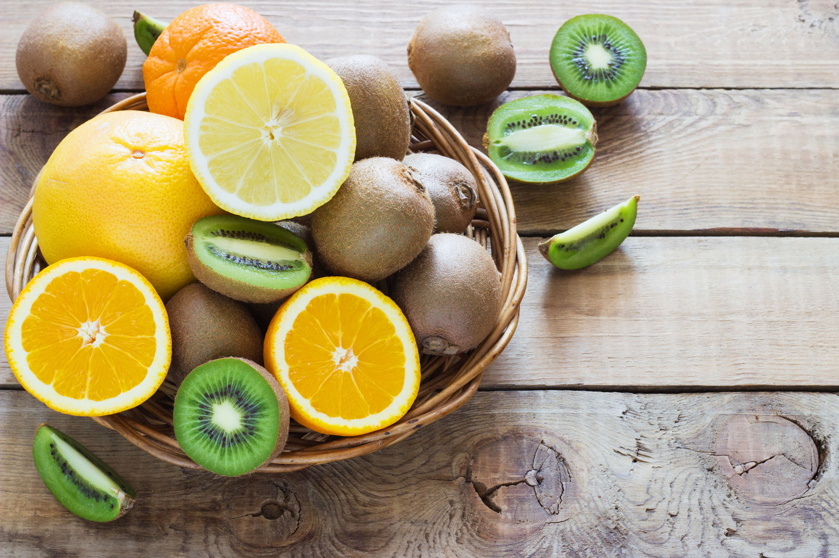 55698244 - fresh juicy citrus fruits in a basket on a wooden background kiwi, orange, lemon, grapefruit