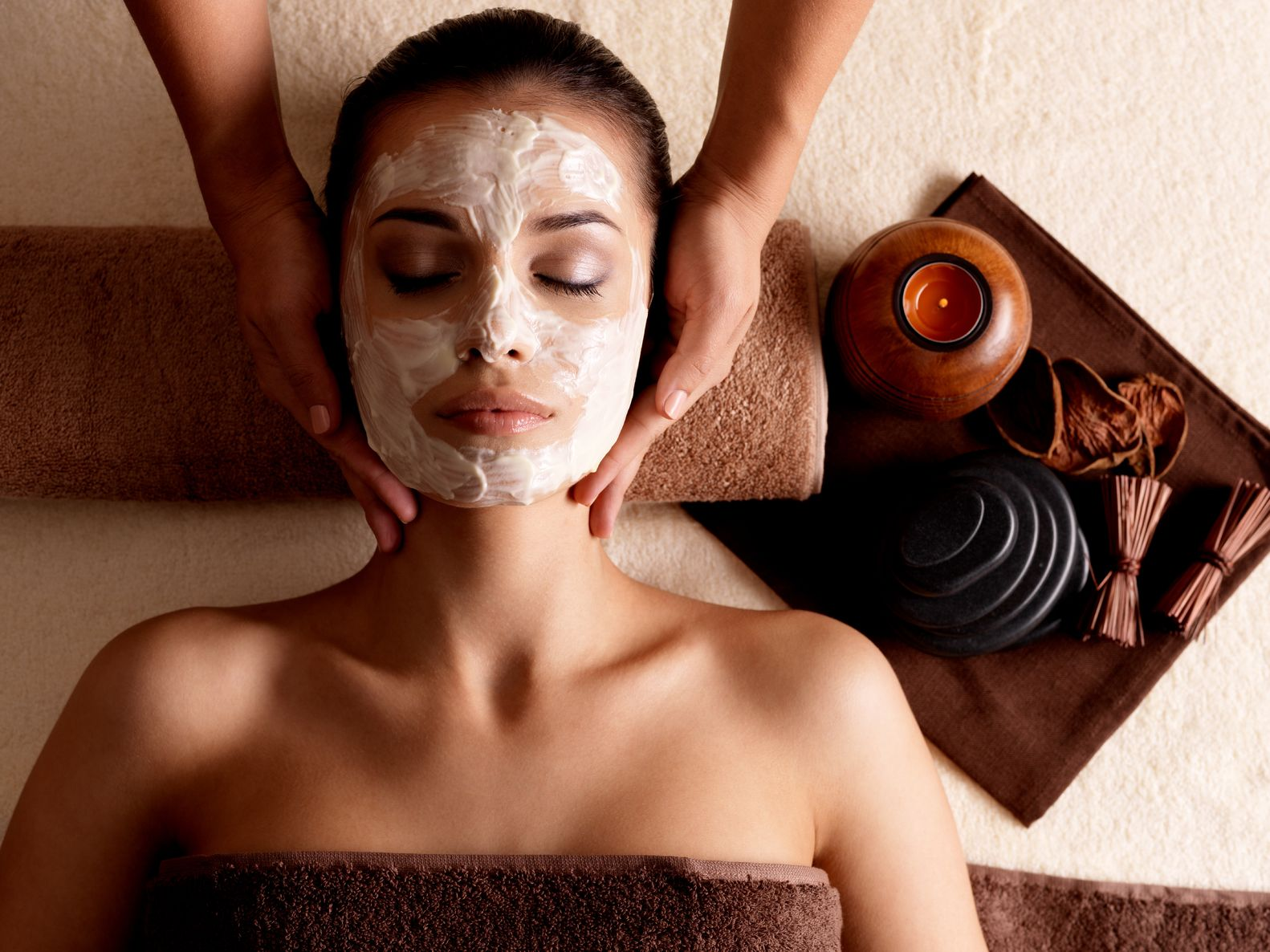 16578470 - spa massage for young woman with facial mask on face - indoors